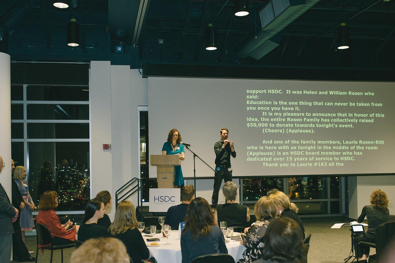 A speaker and interpreter at HSDC's 2017 Cocktails & Connections event, with live captioning behind them.