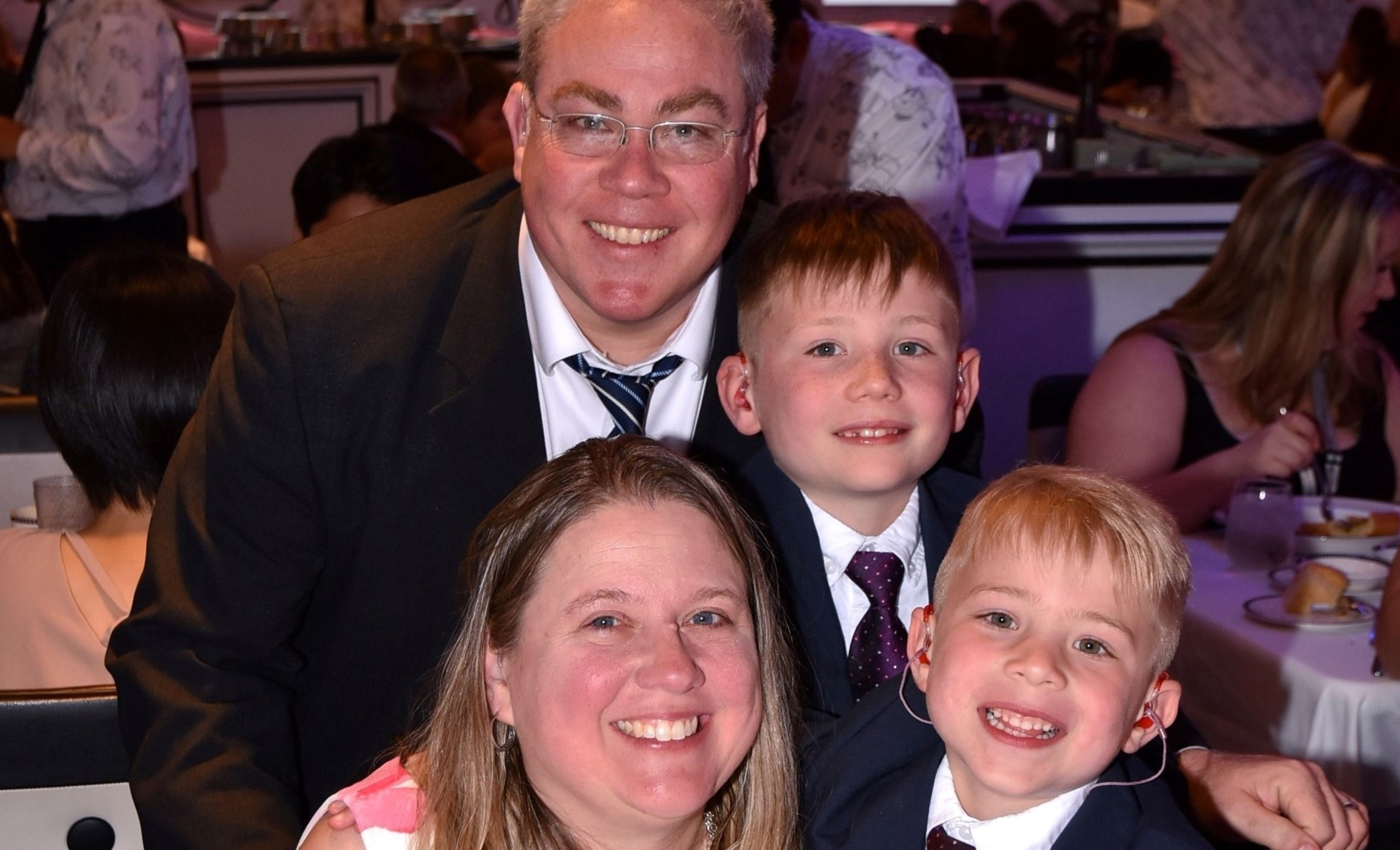 The Gramer family posing for a picture in a restaurant. Father Brendan, mother Laura, and brothers Brett and Luke. They are wearing formal attire.