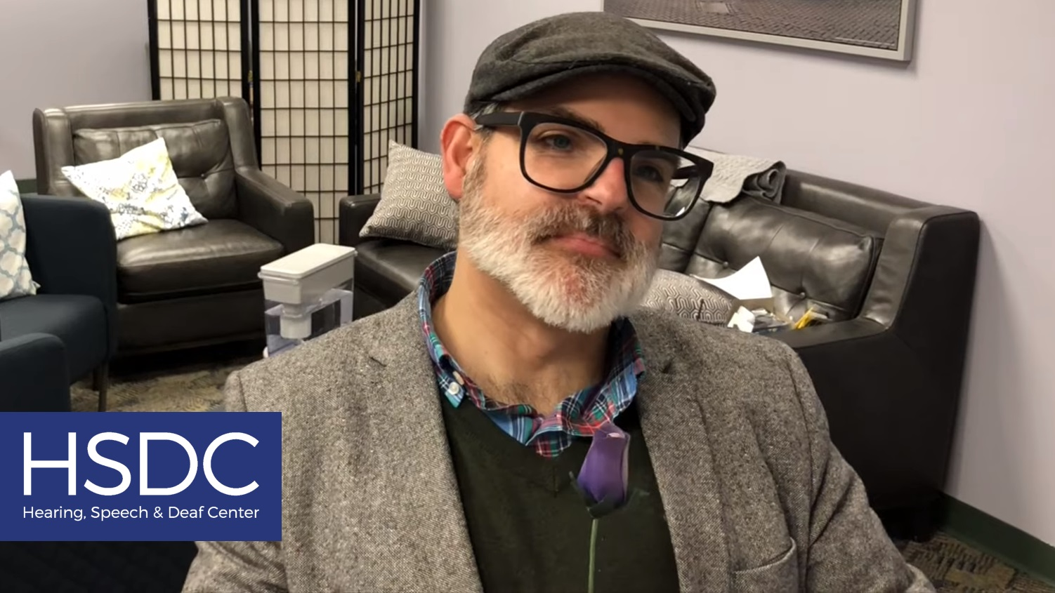 A screenshot of a video. A man with a gray beard, black glasses, grey hat, and grey coat is holding a blue flower and looking offscreen to the right. The HSDC logo is in the bottom left corner.