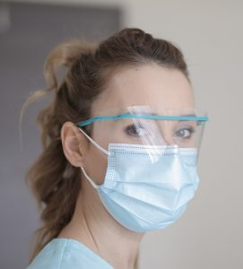 A photo of a light-skinned, feminine-presenting person with brown hair wearing medical eye protectors and a face mask.